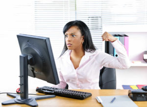 Woman sat at computer looking overwhelmed