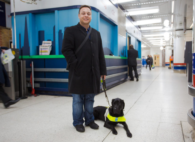Daniel standing in a building with his black guide dog sitting next to him