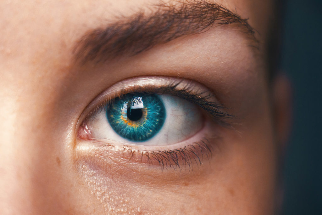 A blue eye of a young woman showing the importance of healthy eyes