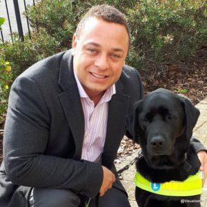 Dan with his arm around his trusty black labrador guide dog Zodiac