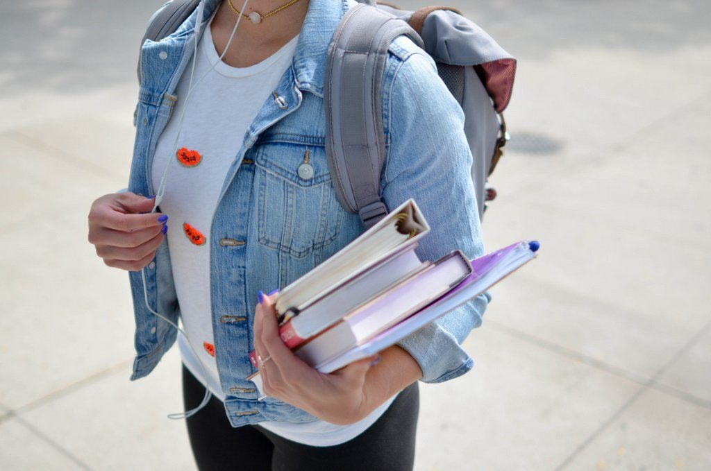Female student in denim jacket holding books
