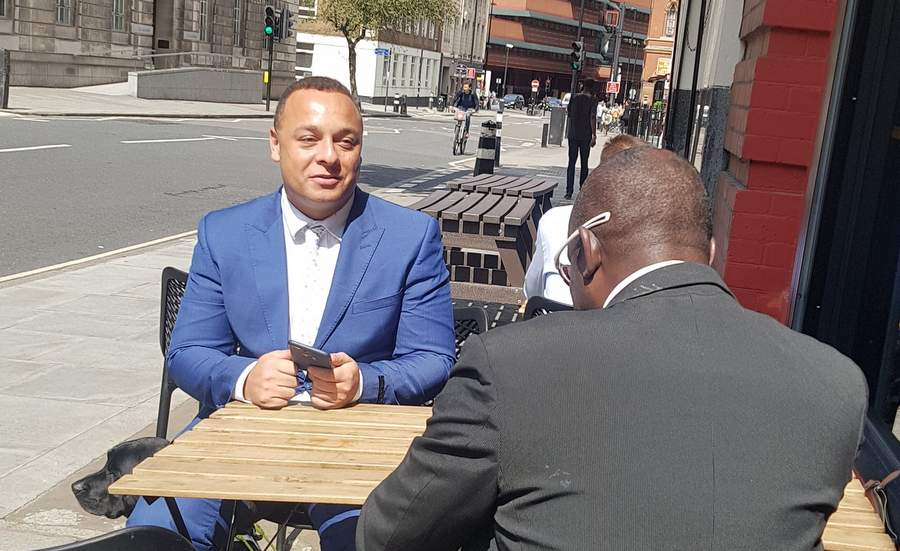 Two men chatting outside a coffee shop