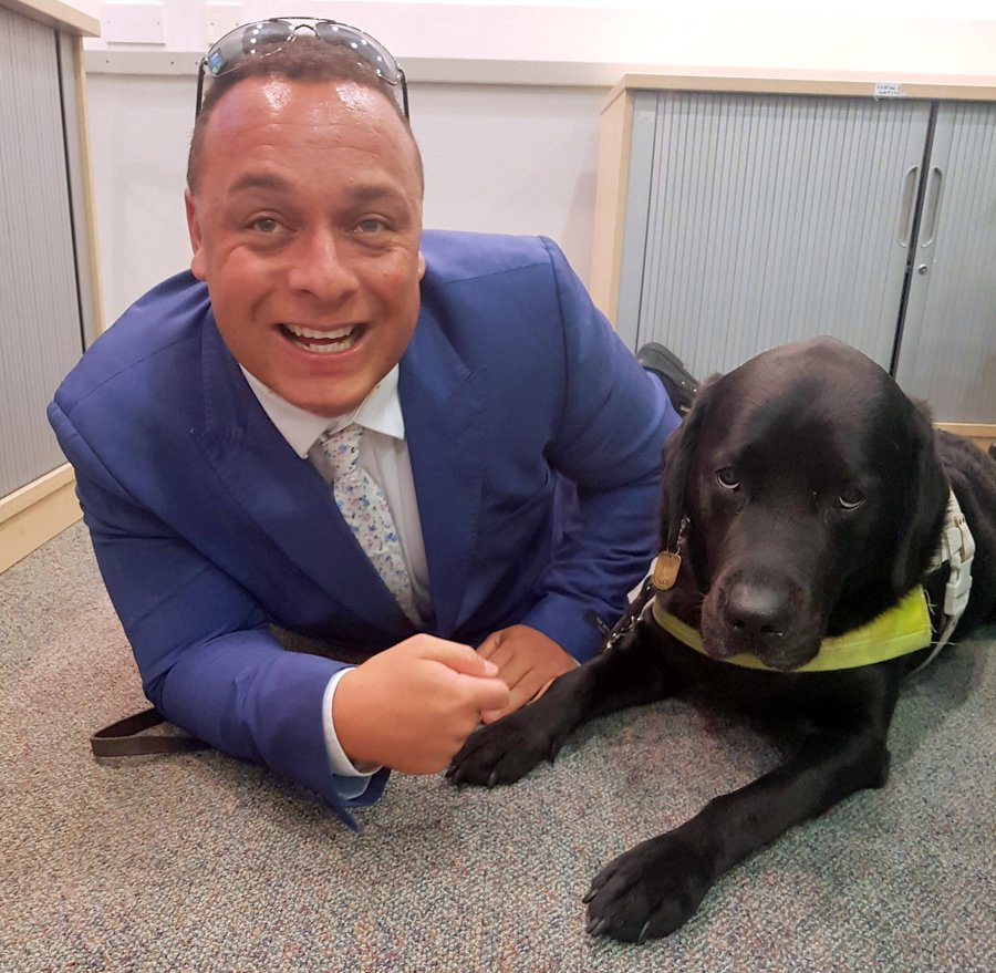 Daniel and his guide dog Zodiac lying on the floor