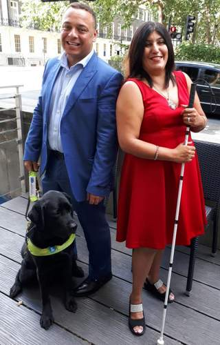 Man and woman with black lab guide dog
