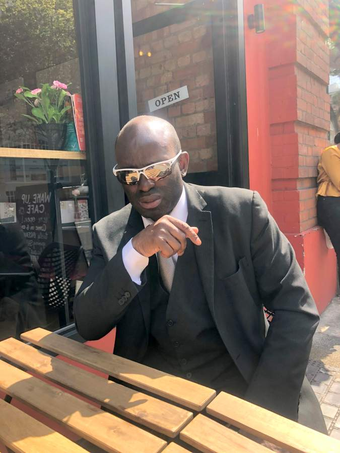Man sat outside a coffee shop looking cool in shades and a suit