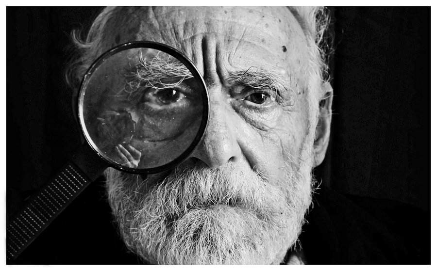 Older man looking through a magnifying glass