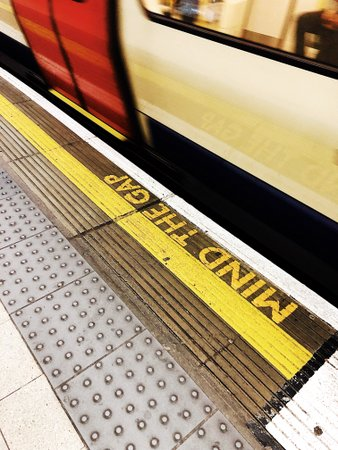 Train at platform with Mind the Gap written on platform in yellow letters. Needs to be accessible to all