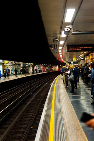 Photo of a rail platform in London at night lit by overhead lighting. People are waiting for the train but how accessible are stations?