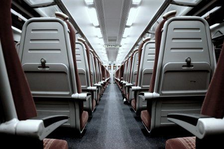Photo of back of train seats taken from inside carriage looking down aisle. No sign of accessible seating