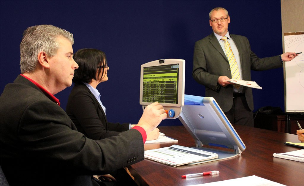 Employee with visual impairment in a meeting using assistive technology to read a document