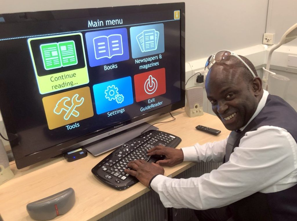 Man with sight loss at workstation with large display screen showing large menu icons. He's smiling as the tech makes his his working life easier.