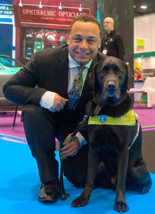 Daniel with his best friend - his black labrador guide dog Zodiac. Together they travel the length and breadth of the UK to increase inclusion and accessibility for people with visual impairments. Dan is wearing a suit and Zodiac has his working harness on.